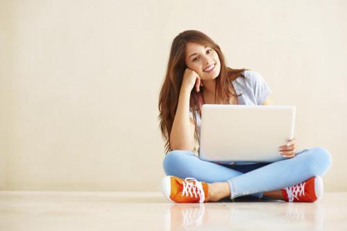 Красивая девушка с ноутбуком в руках