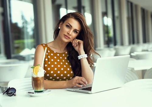 Красивая девушка сидит за столом на котором стоят ноутбук, коктейль и очки