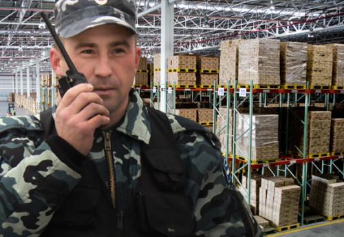 Охранник на складе разговаривает по рации