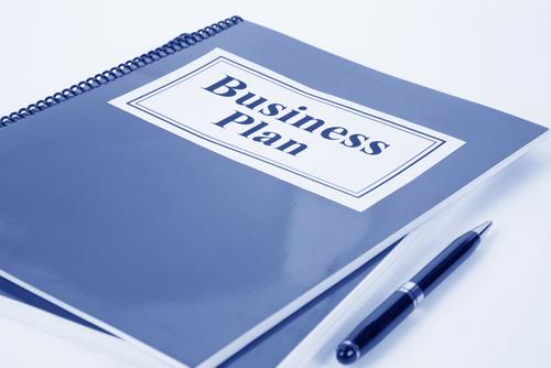 На столе лежат ручка и бизнес-план маленькой фирмы