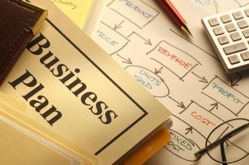 Калькулятор, очки, ручка и бизнес-план лежат на столе