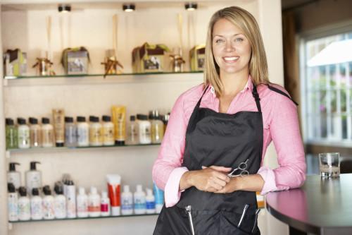 Девушка парикмахер стоит в салоне красоты