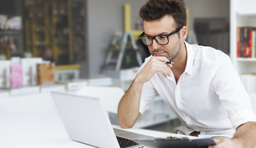 Парень сидит за столом  напротив ноутбука и держит в руках ручку