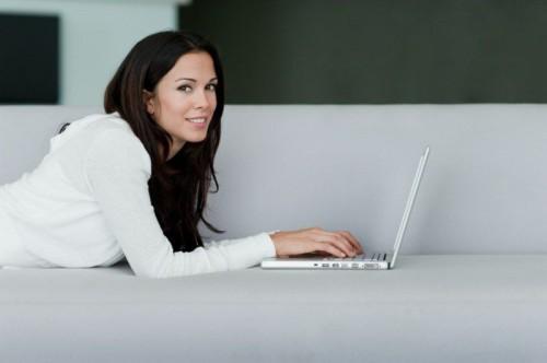 Красивая девушка лежит на диване с ноутбуком