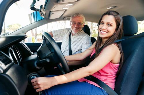 Инструктор учит вождению девушку в своей автошколе