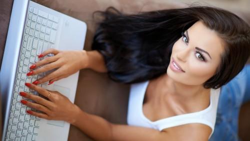 Девушка набирает текст на ноутбуке