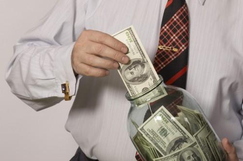 Мужчина вкладывает деньги в банку