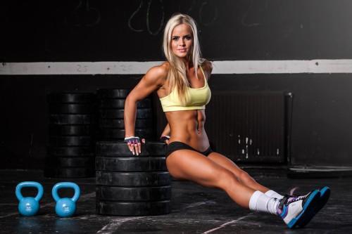 Красивая девушка делает упражнения в фитнес клубе