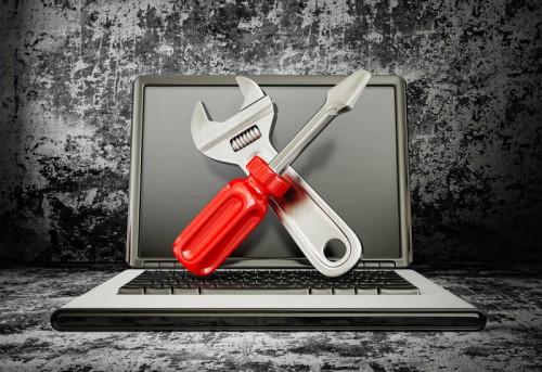 Ноутбук, разводной ключ и отвертка