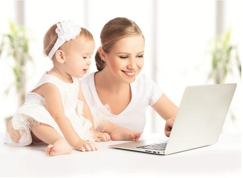 Мама и дочь сидят напротив ноутбука, а мама ищет способы, как заработать в декрете на дому