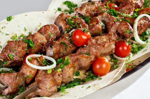 Шашлык из свинины на шампурах с помидорами и луком выложенный на армянском лаваше
