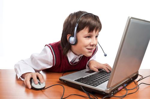 Школьник играет в игру на ноутбуке