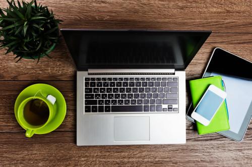 Ноутбук, планшет, смартфон, записная книжка и чашка с чаем