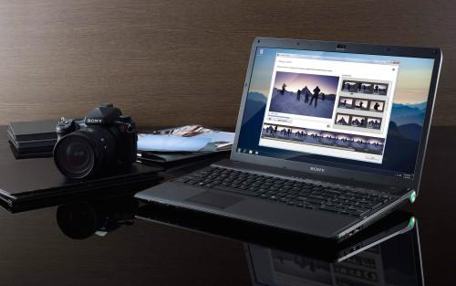 Ноутбук и фотоаппарат лежат на столе