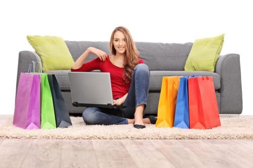 Девушка сидит на полу с ноутбуком в руках, а рядом лежат товары заказанные в интернет-магазине