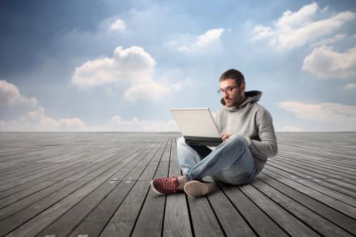 Парень сидит на крыше с ноутбуком в руках