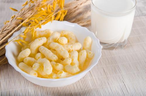 Кукурузные палочки в тарелке, на столе и стакан молока