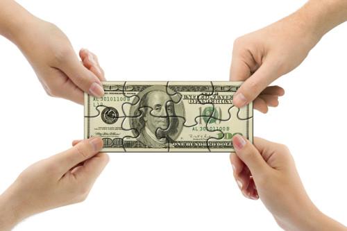 Руки людей держат 100 долларовую купюру