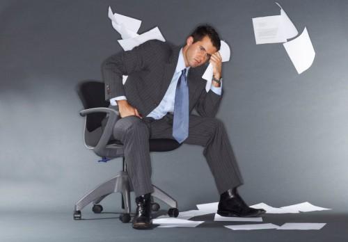 Начинающий бизнесмен сидит на стуле и думает об ошибках, которые совершил