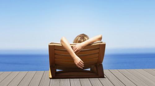Девушка лежит на море в шезлонге