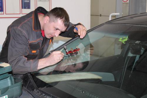 Мастер устраняет скол лобового стекла автомобиля
