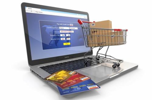 Ноутбук, пластиковые карты, тележка, в которой лежат коробки с товарами из интернет-магазина
