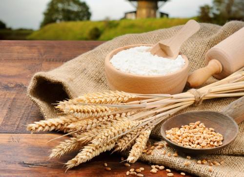 Мука, зерно, скалка и пшеничные колосья лежат на столе