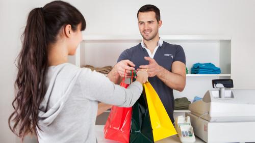 Продавец мужчина продал девушке покупателю одежду