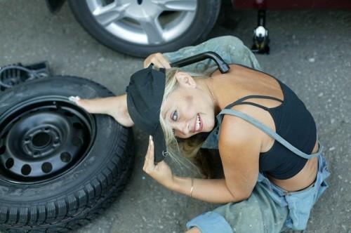 Красивая девушка меняет колесо автомобиля