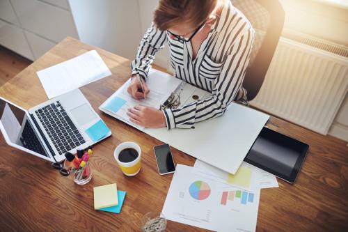 Девушка с помощью ноутбука и данных составляет бизнес-план для своего бизнеса с минимальными вложениями