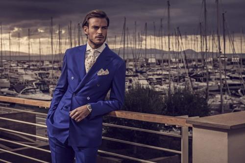 Богатый парень в костюме стоит на пирсе