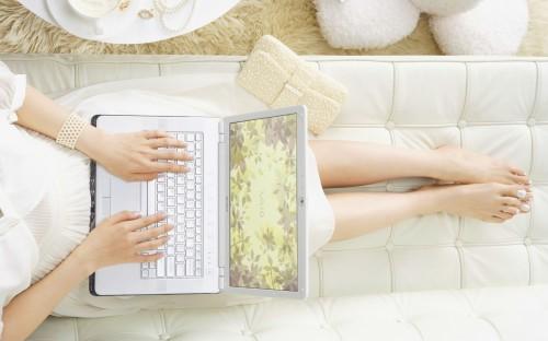 Девушка лежит на диване с ноутбуком в руках и ищет хорошие методы заработка в сети