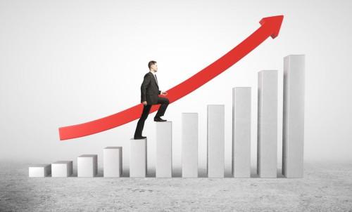 Мужчина в костюме идёт вверх по ступенькам навстречу своему выгодному бизнесу