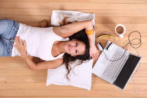 Девушка лежит на полу, а рядом с ней ноутбук и чашка с кофе