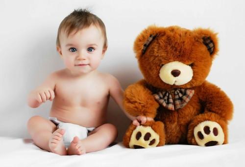 Маленький ребенок в памперсе и мягкая игрушка мишка