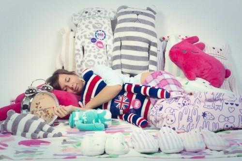 Девушка спит на кровати в окружении мягких креативных игрушек