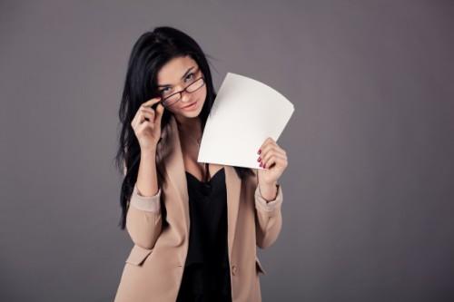 Девушка в очках держит в руке листы бумаги, на котором хочет записать список идей без вложений