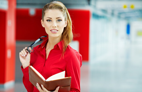 Красивая девушка держит в руках очки и записную книжку