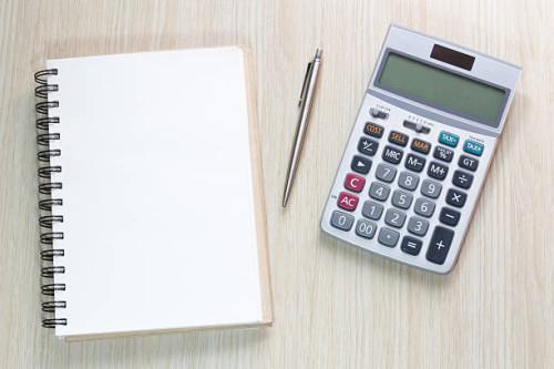 Калькулятор, ручка и блокнот лежат на столе