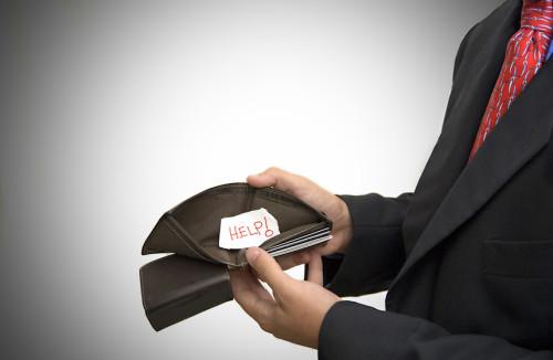 Мужчина держит в руке пустой бумажник для денег