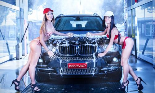 Две девушки, работницы автомойки моют машину