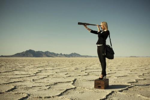 Девушка в пустыне смотрит в подзорную трубу