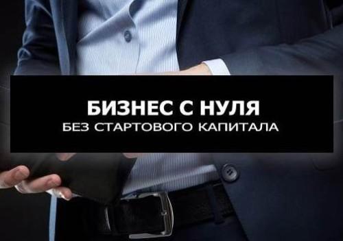 Мужчина в костюме держит в руках пустой бумажники и надпись бизнес с нуля без стартового капитала