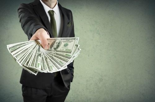 Мужчина в костюме даёт деньги в долг