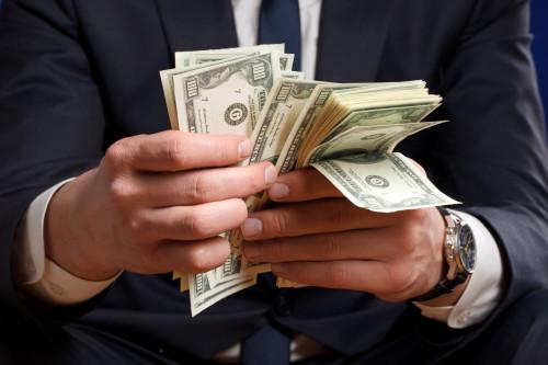 Мужчина в костюме держит в руках деньги, 100 долларовые купюры