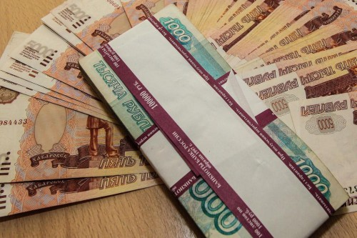 Деньги, тысячные и пятитысячные купюры лежат на столе
