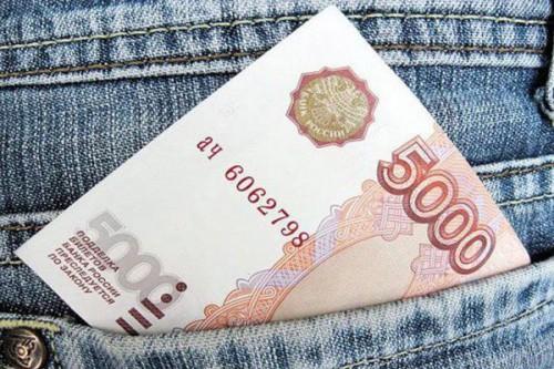 Пятитысячная купюра торчит из кармана джинсов