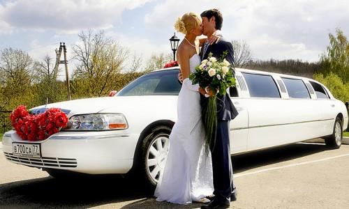 Молодожёны целуются на фоне белого лимузина