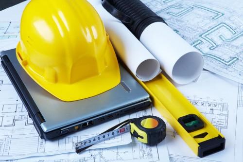Инструменты строителя - рулетка, уровень, каска, ноутбук лежат на чертежах