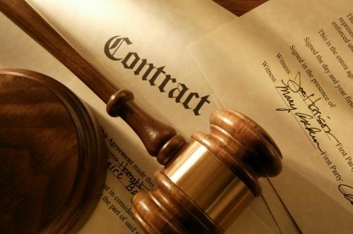 Документы с надписью контракт и молоток